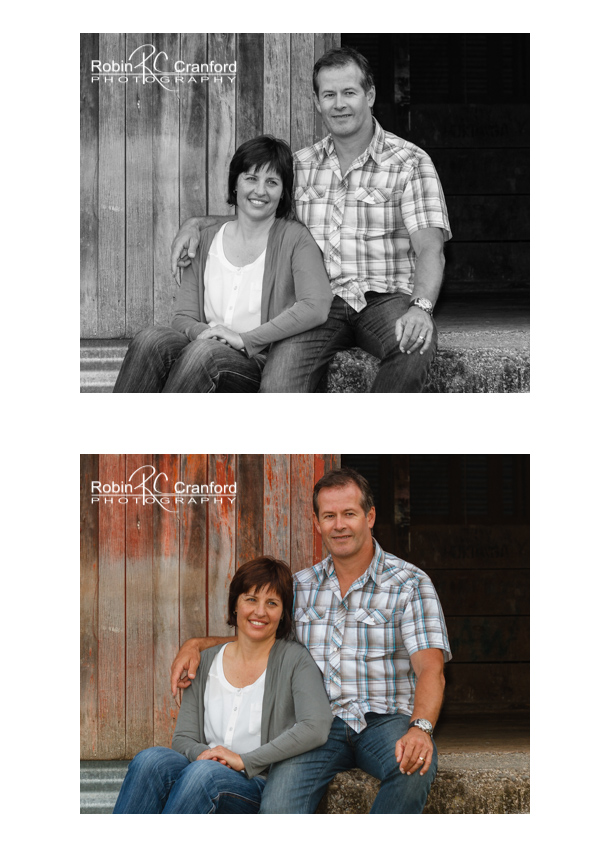 Couple posed in front of red barn door.
