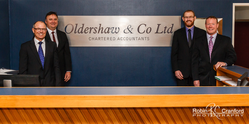 Corporate group portrait of 4 men in suits.
