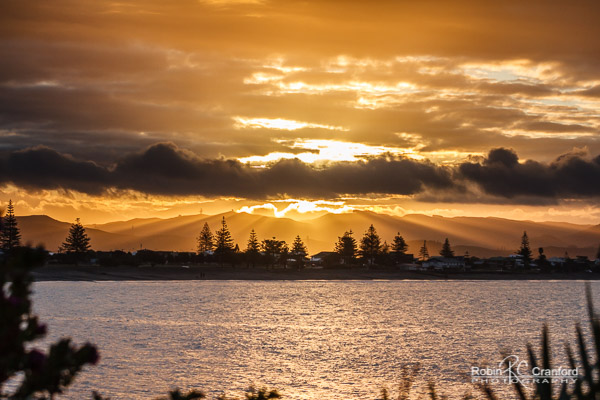 Golden sunset with god rays over Westshore, Napier, Hawke's Bay, New Zealand.