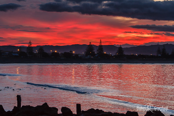 A blazing pink sunset over Westshore, Hawke's Bay, New Zealand.
